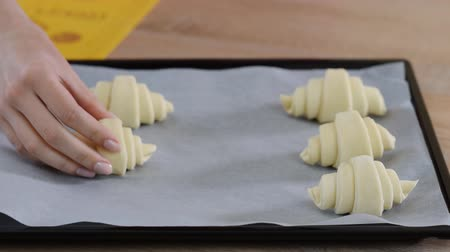 レイヤード : Female cook arranging croissants on a cooking tray at the kitchen. Cooking farinaceous foods in a bakery.