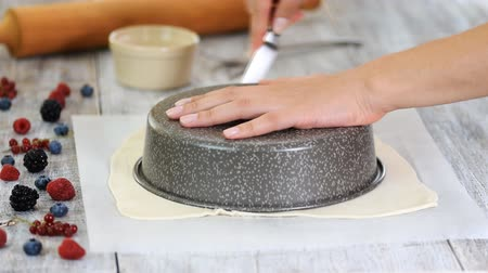 дрожжи : Cook cutting dough into circle for home made baking. Woman cutting raw dough on the parchment paper with a knife.