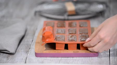 batido : Female hands taking square mousse cakes out of a flexible silicone mold, close-up.