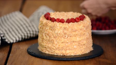 migalha : Confectioner decorates Napoleon Layered Cake With fresh Raspberry.