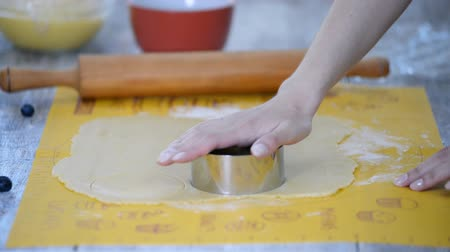 baking ingredient : Metal cutter cutting out circles of fresh pastry for tarts. Stock Footage
