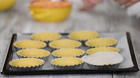 ervilhas : Pastry chef making tartlets. Confectioner cover each tartlet with small sheet parchment and fill with dried peas. Process of baking. Vídeos