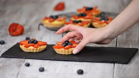 tartlet : Beautiful delicious summer tartlets with fresh custard creamy filling topped with strawberry and blueberry. Stock Footage