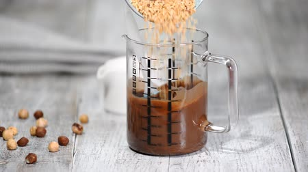 фундук : Add the nuts to the melted chocolate. Confectioner making chocolate nut glaze. Стоковые видеозаписи