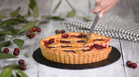 песочное печенье : Womens hands cut a homemade Cherry Pie with a Flaky Crust.
