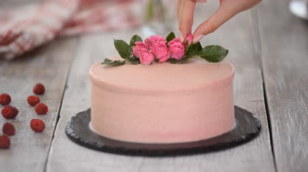 elegant dessert : Confectioner pastry chef decorates creamy pink cake with fresh flowers on table