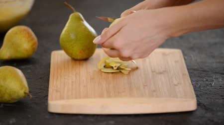 soyulmuş : Woman peeling pear for dessert over table. Stok Video