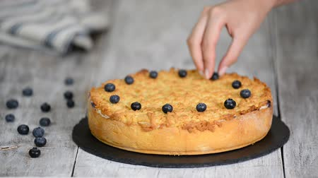 servido : The woman adorns the crumble cake with blueberry. Sweet food. Stock Footage