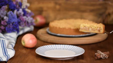apple pie : Female hands put a piece of apple pie on a plate.