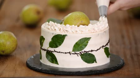 caramelo : Decorating a cake with cream using piping bag. Woman confectioner makes chocolate cake with pear. Vídeos