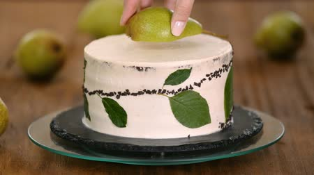 šlehačka : Girl confectioner decorates chocolate cake with fresh pear. The concept of homemade pastry, cooking cakes.