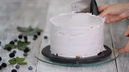 decorating : Confectioner smooths purple cream on a biscuit cake with a cooking spatula. The concept of homemade pastry, cooking cakes.