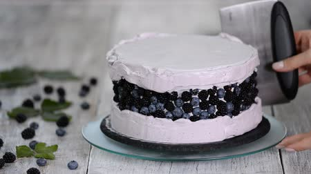 smetanový : Confectioner smooths purple cream on a biscuit cake with a cooking spatula. The concept of homemade pastry, cooking cakes.