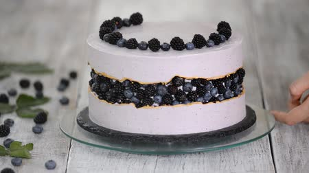 amoras : Confectioner decorates a beautiful cake with blueberries and blackberries.