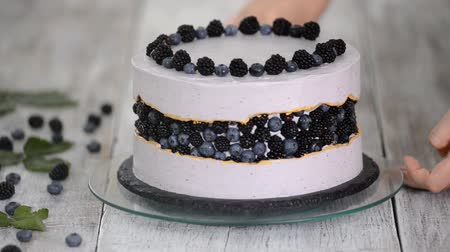 kek : Confectioner decorates a beautiful cake with blueberries and blackberries.