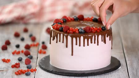 смородина : Confectioner decorates with berries a biscuit cake with pink cream and chocolate. Cake stands on a wooden stand on a white table. The concept of homemade pastry, cooking cakes. Стоковые видеозаписи