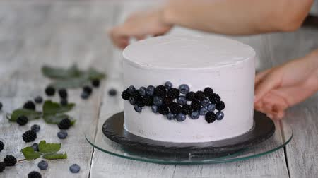 koláč : Confectioner decorates a beautiful cake with blueberries and blackberries.