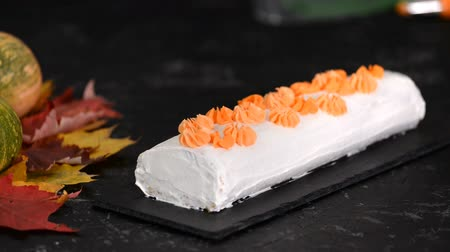 baked pumpkin : Woman decorates pumpkin roll with cream cheese. Stock Footage