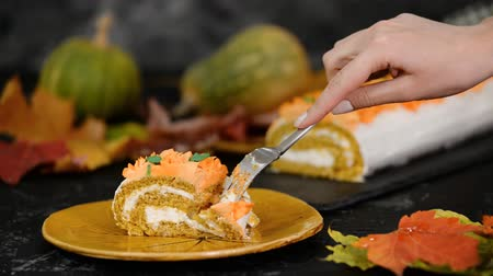 baked pumpkin : A woman eat piece of delicious pumpkin roll with cream cheese.