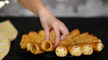 pasta sfoglia : Woman hands pipe the cream into each end of the horn rolls. Woman making puff rolls with cream.