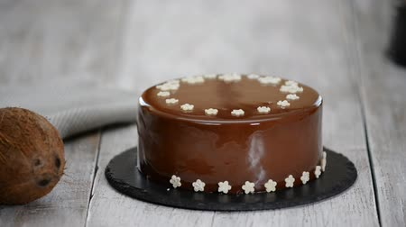 무스 : Woman decorates chocolate mousse cake. Chocolate mousse cake with mirror glaze.