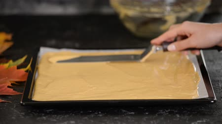 スプレッド : Woman spreads the batter on a baking sheet.