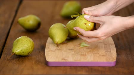 off : Woman Peeling Pear For Dessert Over Table.