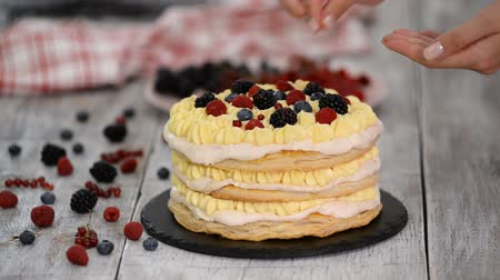 blueberry cheesecake : Confectioner girl puts summer berries on a creamy layer cake. Woman preparing a cake with cream and berries. Stock Footage