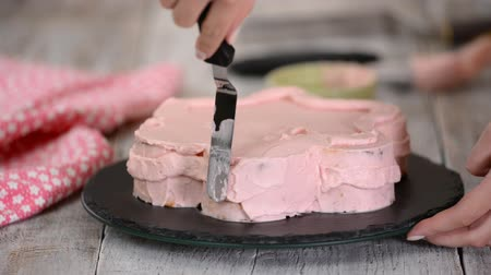 açoitado : Pastry chef is making a pink cake in the shape of a flower. Series.
