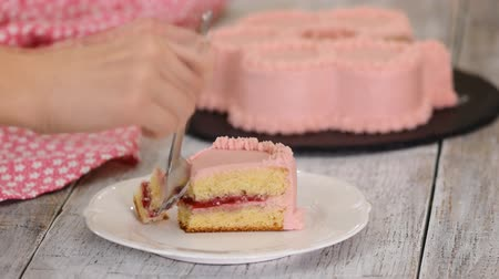 мусс : Eating a piece of raspberry cake with pink cream.