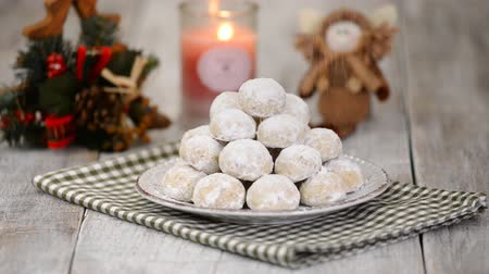 kaplanmış : Traditional Christmas snowballs cookies, biscuits covered sugar powder. Sprinkle cookies with powdered sugar. Christmas New Year festive ornament decorations. Stok Video