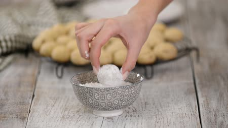 puffs : Female hands roll cookies in powdered sugar.