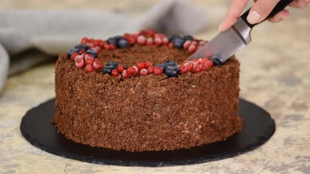 сладость : Woman cuts with knife Russian Chocolate Cake Napoleon. Chocolate Napoleon cake of puff pastry with Berries