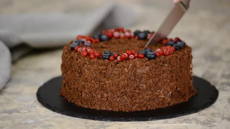 смородина : Woman cuts with knife Russian Chocolate Cake Napoleon. Chocolate Napoleon cake of puff pastry with Berries.