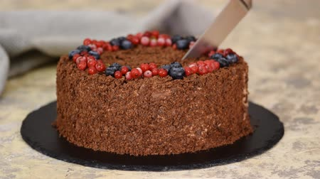 сладость : Woman cuts with knife Russian Chocolate Cake Napoleon. Chocolate Napoleon cake of puff pastry with Berries.