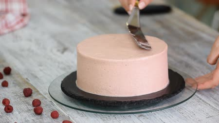 chefs table : Hands of female confectionery chef using pastry scraper and rotating cake stand to decorate handmade cake with pink cream frosting in kitchen.