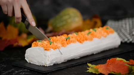 baked pumpkin : Female hands cutting pumpkin roll cake. Cut a piece of sweet dessert.