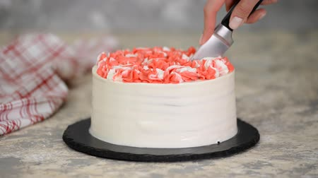 çırpılmış : The knife cuts a piece of delicious cherry cake with pink cream.