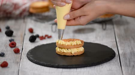 kuchařský : Pastry chef making French Mille Feuille with custard and berries. French dessert millefeuille of puff pastry and custard cream.
