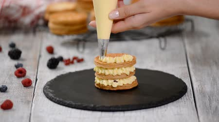 vla : Pastry chef making French Mille Feuille with custard and berries. French dessert millefeuille of puff pastry and custard cream.