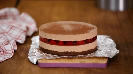 мусс : Dusting a delicious chocolate mousse cake with cocoa powder.