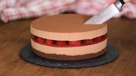 black raspberry : Womans hands cut the delicious chocolate mousse cake with raspberries jelly.