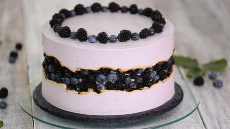blackberry : Purple beautiful cake decorated with berries, blackberries and blueberries on top.