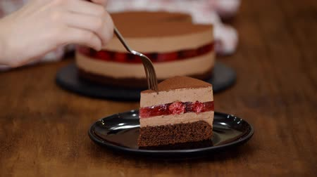 šlehačka : Woman eating piece of delicious chocolate mousse cake with raspberries jelly.