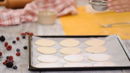 fuvalom : A baker uses a sifter to sprinkle powdered sugar on puff pastry. Making French Mille Feuille at kitchen.