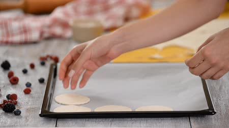 bafat : Female hands puts round cut cookies on baking sheet.