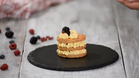 смородина : Pastry chef making French Mille Feuille with custard and berries. French dessert millefeuille of puff pastry and custard cream.