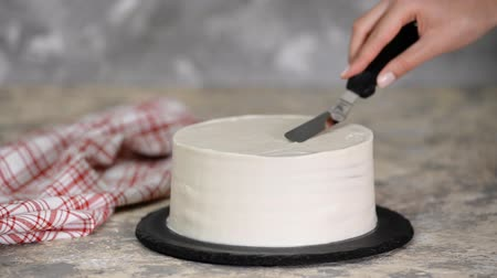 слоистых : A confectioner finishes spreading cream over a cake standing.
