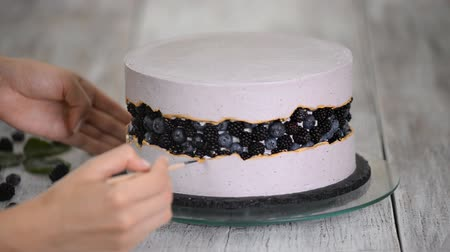 blackberry : Confectioner decorates a berries cake with gold syrup, handmade.