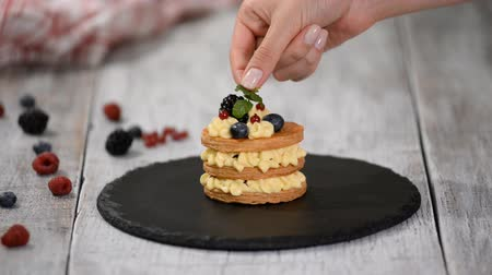 napoleone : Pastry chef making French Mille Feuille with custard and berries. French dessert millefeuille of puff pastry and custard cream.
